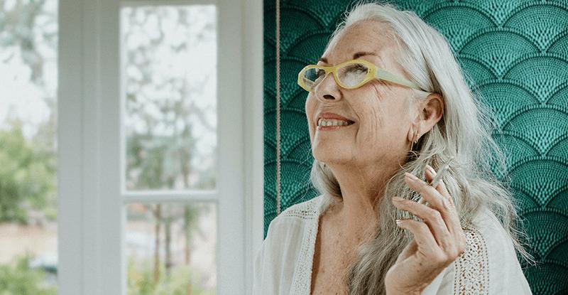 Usmiata stará pani s bielymi vlasmi a okuliarmi v rukách drží cigaretu s lekárskou marihuanou teda joint