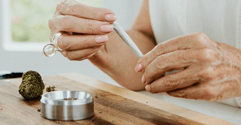 Stará pani v rukách drží cigaretu s lekárskou marihuanou teda joint a na drevenom stole je položená drvička a lekárska marihuana