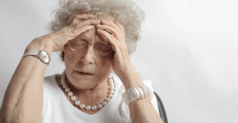 Stará pani s bielymi vlasmi a okuliarmi sa drží za hlavu od bolesti a trápenia
