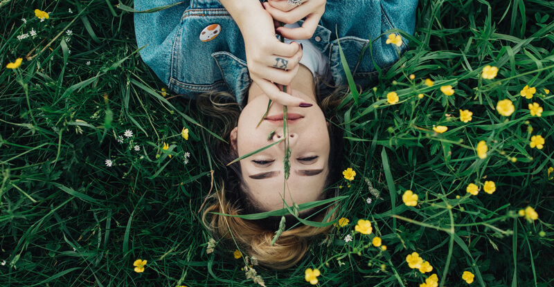 Mladá žena leží na lúke a usmieva sa