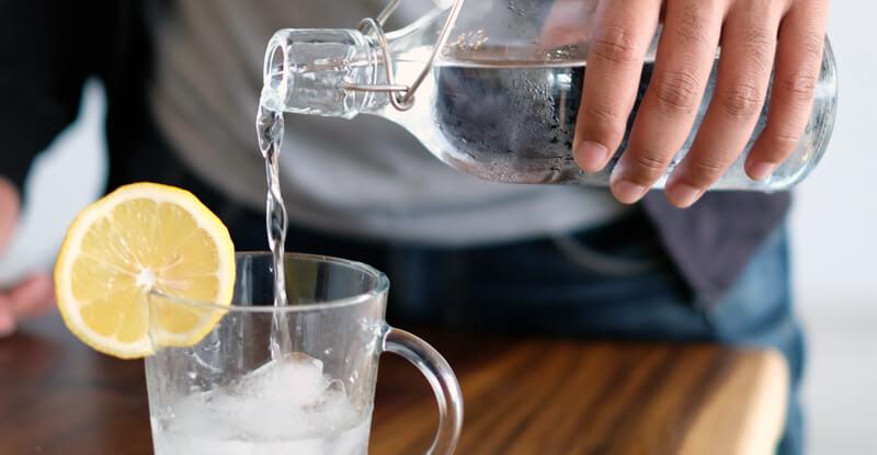 Nalievanie vody zo sklenenej fľaše do pohára