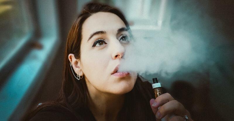Vaporizácia - mladá žena vydychuje paru z vaporizéra