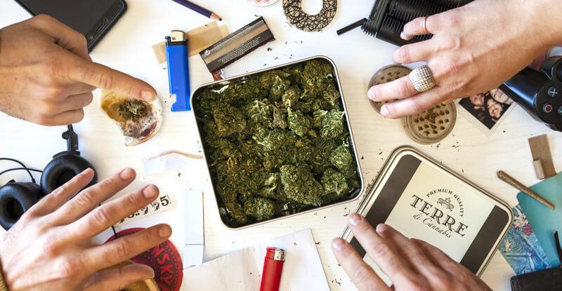 Vaporizovanie: ilustračný obrázok - na stole okolo krabičky so šiškami marihuany sú rozložené rozličné predmety (cigaretové papieriky, vaporizér, zapaľovače...) a naťahujú sa za nimi štyri ruky, pohľad zhora
