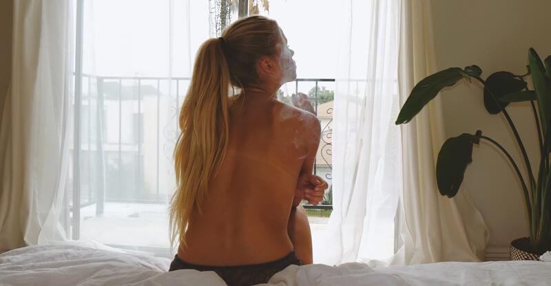Krásna mladá žena sedí na okraji postele a fajčí